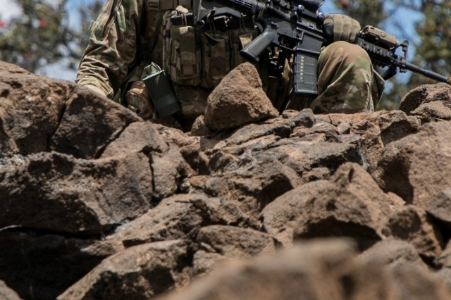 U.S. Army 1st Lt. Bret Brunco assigned to 2nd Squadron, 14th Calvary Regiment, 2nd Infantry Brigade Combat Team, 25th Infantry Division calls out to his platoon during a Combined Arms Live Fire Exercise (CALFEX) at Pohakuloa Training Area, Hawaii, May 15, 2018. The CALFEX utilizes all the enablers available to the unit in order to increase interoperability, concentrate combat power and mass effects on the objective. (U.S. Army photo by 1st Lt. Ryan DeBooy)