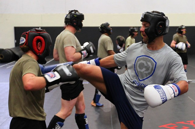 Guest instructor and former MMA fighter Josh Koscheck, right, shows Cpl. Samantha Lamirand, 1st Engineer Battalion, 1st Armored Brigade Combat Team, 1st Infantry Division, combat engineer, how to block a kick and move in closer to an attacker to throw a punch April 18 during the advanced striking techniques portion of the Combatives Master Trainer Course held on Fort Riley, Kansas, during the month of April. (Chad L. Simon, 1st Inf. Div. Public Affairs)