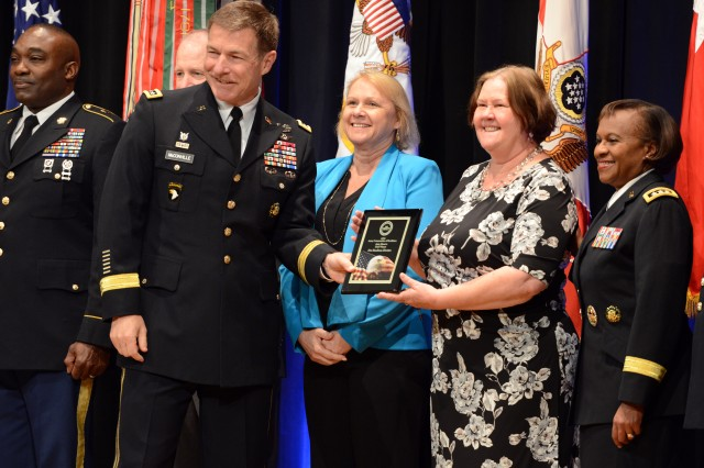 Vice Chief of Staff of the Army Gen. James C. McConville presents the Gold award to 81st Readiness Division, Fort Jackson, S.C., leaders at the Army Communities of Excellence Awards ceremony at the Pentagon, May 18, 2018. Lt. Gen. Gwen Bingham, assistant chief of staff for Installation Management (right), also participated in the ceremony.