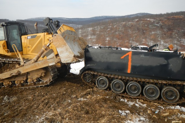 A bulldozer moves a 13-ton M106 mortar carrier into position on Cranberry Mountain near West Point, New York, during winter as part of an ongoing project to emplace heavy targets on the post's indirect-fire range.