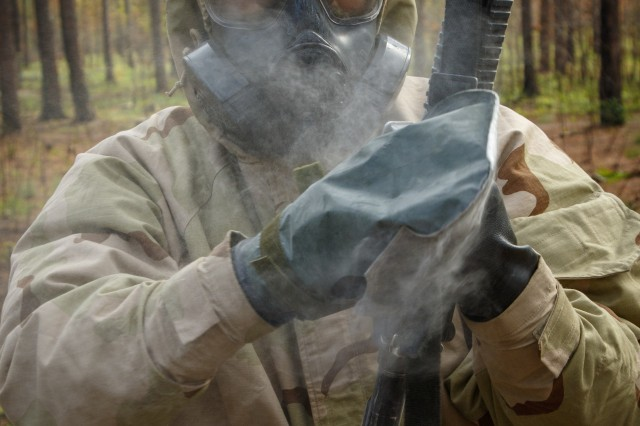 U.S. Army Spc. Joseph Culbertson, a platoon medic assigned to Company D., 1st Battalion, 505th Parachute Infantry Regiment, 3rd Brigade Combat Team, 82nd Airborne Division, decontaminates his weapon after receiving a mock chemical attack during the 18th Airborne Corps hosted Expert Field Medic Badge testing, May 16, at the Medical Support Training Center on Fort Bragg, North Carolina. During the EFMB testing, individual Soldiers are graded on several aspects of being in a medical field. Each event falls under one of four major groups; Tactical combat casualty care, casualty evacuation, radio communication and warrior skills. (U.S. Army photo by Sgt. Christopher Gallagher)