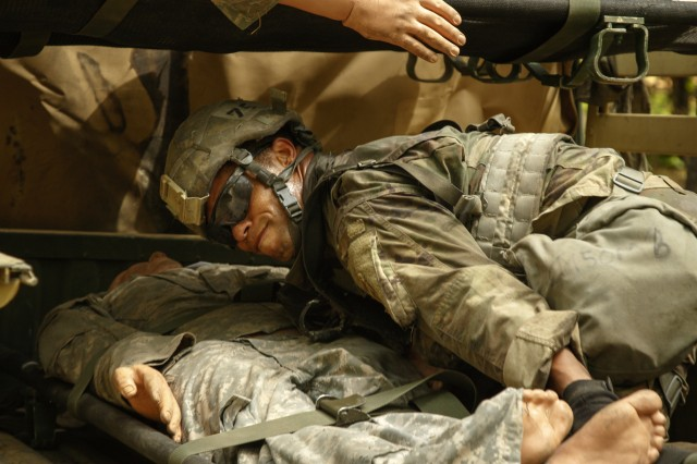 U.S. Army Sgt. Alex Pickens, a lab technician assigned to the Brigade Support Battalion, 3rd Brigade Combat Team, 82nd Airborne Division, positions and secures a mock casualty in the back of a military vehicle during the Expert Field Medic Badge testing, May 16, at the Medical Support Training Center on Fort Bragg, North Carolina. During EFMB, individual Soldiers are graded on several aspects of being in the medical field. Each event falls under one of four major groups; Tactical combat casualty care, casualty evacuation, radio communication and warrior skills. (U.S. Army photo by Sgt. Christopher Gallagher)