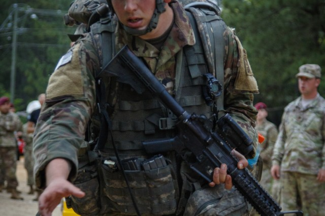 A U.S. Army paratrooper assigned to the 82nd Airborne Division reaches for a cup of water during the 12-mile foot march portion of the Expert Field Medic Badge testing, May 18, on Fort Bragg, North Carolina. With an average passing rate of 18 percent, the EFMB is one of the most difficult and prestigious Army special skill badges medical professionals can earn. (U.S. Army photo by Sgt. Christopher Gallagher)