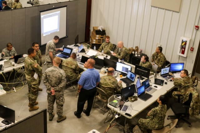 Members of a network defense cell review the team's performance May 18, 2018 during the culminating exercise of Cyber Shield 18, a two week long event at Camp Atterbury, Ind. More than 800 Soldiers, Airmen, federal and state agencies, and civilian partners from 40 states and territories traveled across the country as part of the National Guard's ongoing effort to advance Guard readiness to respond to real-world cyber incidents.