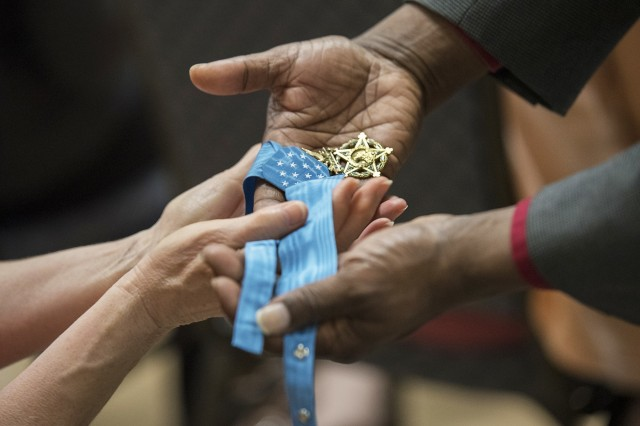 Army civilian employees pass around Retired Master Sgt. Leroy Petry's Medal of Honor while attending a Mental Health Awareness Observance May 17, Heritage Hall, Rock Island Arsenal, Illinois. Petry asked the audience to pass around his medal while he served as one of the keynote speakers during the event.