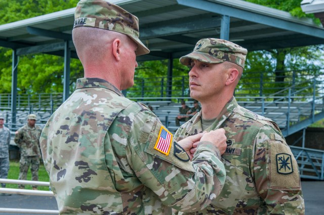 Maj. Gen. Kent Savre, MSCoE and Fort Leonard Wood command general pins an Army Commendation Medal on Joint Service Noncommissioned Officer of the Year, Sgt. 1st Class Johnathon Balcom, during the installation's 2018 Best Warrior Competition awards ceremony.