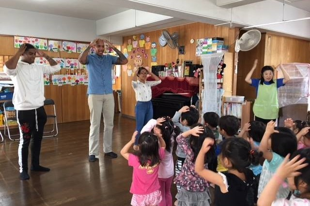 "From left to right, Spc. Isaiah Benberry, Spc. Temujin Benton and Spc. Kathy Bounkanha, sing ""Head, Shoulders, Knees and Toes"" with Japanese children at a local preschool April 26 in Yomitan, Okinawa, Japan."