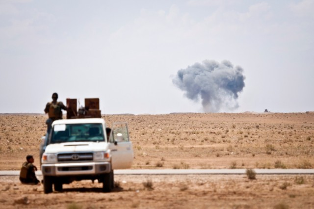 Syrian Democratic Forces watch as a coalition airstrike hits its target on a known Islamic State of Iraq and Syria location near the Iraq-Syria border, May 13, 2018. The SDF forces provided security for a coalition mortar team and were postured to offer quick response force services if needed. The strike was in support of Operation Roundup, the offensive to eliminate pockets of ISIS fighters in the Middle Euphrates River Valley in Syria.