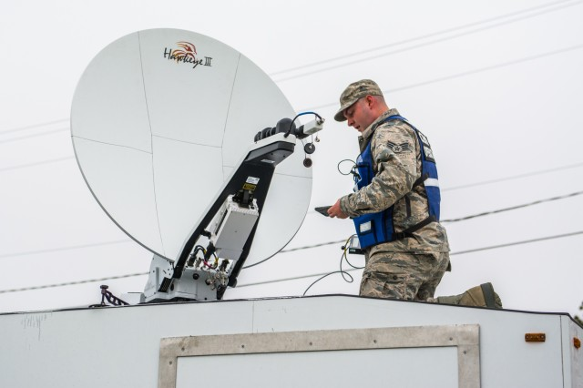 An senior airman sets up communications on top of a specially designed trailer at Joint Base Cape Cod, Buzzards Bay, Massachusetts May 15, 2018.  They are taking part in a joint forces exercise intended to test the New England Chemical Biological Radiological Nuclear (CBRN) Enhanced Response Package's (CERF-P) response to a CBRN event.  Soldiers and Airmen from Maine, Vermont, New Hampshire, Rhode Island, and Massachusetts are participating.  Each team will be scored on their performance and will help the units gage their readiness in case of a real emergency.