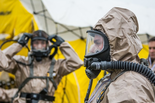 Soldiers fully dawn their protective masks and suits in preparation of a joint exercise intended to test the New England Chemical Biological Radiological Nuclear (CBRN) Enhanced Response Package's (CERF-P) response to a CBRN event at Joint Base Cape Cod, Buzzards Bay, Massachusetts May 15, 2018.  Soldiers and Airmen from Maine, Vermont, New Hampshire, Rhode Island, and Massachusetts are participating.  Each team will be scored on their performance and will help the units gage their readiness in case of a real emergency.
