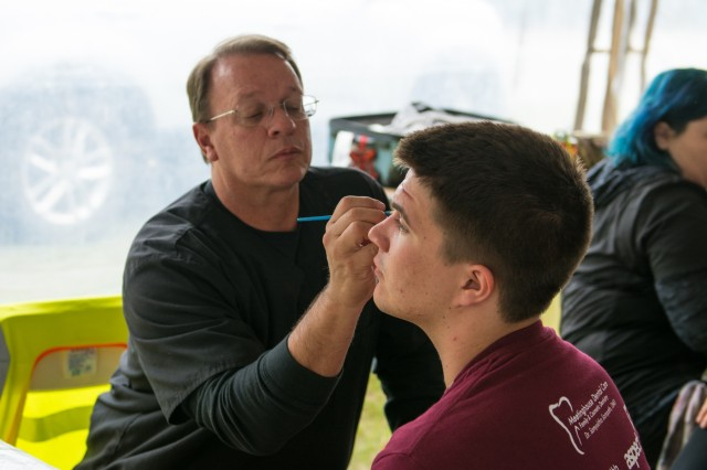 A professional make-up artist applies mock injuries to actors pretending to be casualties as part of an exercise to test the New England Chemical Biological Radiological Nuclear (CBRN) Enhanced Response Package's (CERF-P) response to a CBRN event at Joint Base Cape Cod, Buzzards Bay, Massachusetts May 16, 2018.  Soldiers and Airmen from Maine, Vermont, New Hampshire, Rhode Island, and Massachusetts are participating.  Each team will be scored on their performance and will help the units gage their readiness in case of a real emergency.