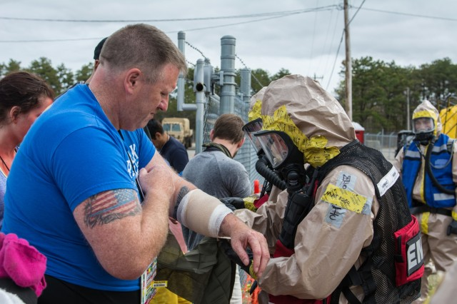 A Soldier wraps a mock injury of an actor pretending to be a casualty as part of an exercise to test the New England Chemical Biological Radiological Nuclear (CBRN) Enhanced Response Package's (CERF-P) response to a CBRN event at Joint Base Cape Cod, Buzzards Bay, Massachusetts May 16, 2018.  Soldiers and Airmen from Maine, Vermont, New Hampshire, Rhode Island, and Massachusetts are participating.  Each team will be scored on their performance and will help the units gage their readiness in case of a real emergency.  If they are ruled proficient in all their tasks, their team will become rectified.