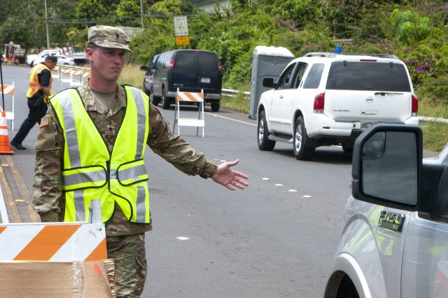 Spc. Donavan Wills, Bravo Co., 227th Brigade Engineer Battalion, directs traffic May 12, 2018 in response to the volcano eruption, at Leilani Estates, Pahoa, Hawaii. Members of the Hawaii Army National Guard are supporting local authorities in an effort to improve safety and security in the impacted neighborhoods.