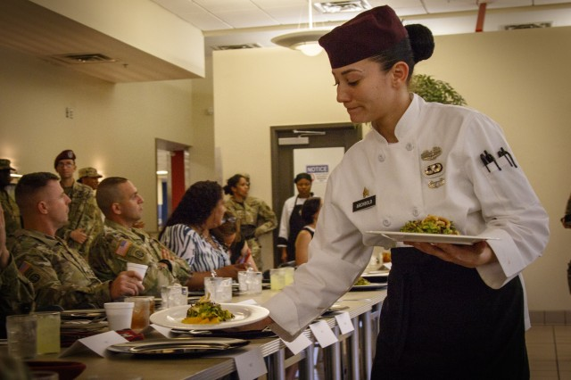 U.S. Army Sgt. Daniela Archbold, a culinary specialist, assigned to Headquarters and Headquarters Company, 307th Brigade Support Battalion, 1st Brigade Combat Team, 82nd Airborne Division, presents and serves one of the three courses during the chef competition during All American Week XXIX May 21, 2018, at Fort Bragg, North Carolina. The chef competition is only one of several events and competitions that takes place during All American Week. (U.S. Army photo by Sgt. Christopher Gallagher)