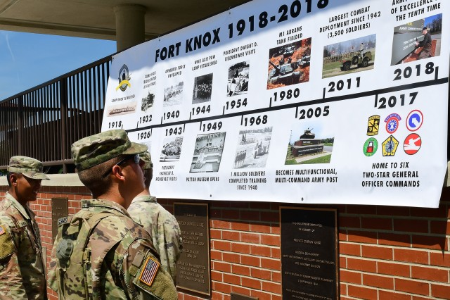 Soldiers read up on the 100-year history of Fort Knox prior to participating in the historic photo shoot on Brooks Field May 23, 2018.