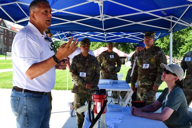 Charles Cline, special projects officer at the Fort Knox Directorate of Plans, Training, Mobilization and Security, goes over details of the photo shoot with key staff members, who were appointed to make sure the participants set up in the right configuration.