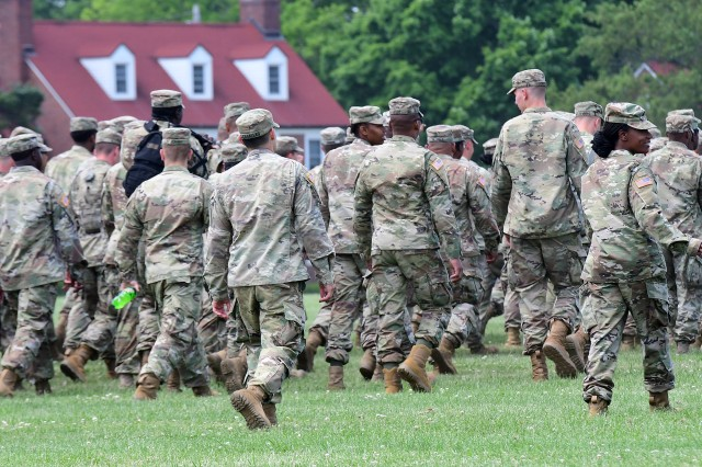 Soldiers move to their designated spots on Brooks Field prior to taking the centennial photo May 23, 2018. Over 1,200 troops participated in the event.