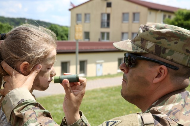 Sgt. 1st Class Edgar Angulo instructs school children from the Hohenfels Elementary School the proper way to apply camouflage face paint during Job Shadow Days at Hohenfels Training Area, Hohenfels, Germany, May 15, 2018. Job Shadow Days is an annual three-day event where school children from both the Hohenfels Elementary School, and Hohenfels Middle/High School are shown various military occupational skills that are present at HTA.