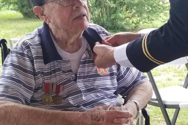 "Security Assistance Command's Chaplain (Col.) Robert Nay pins on awards for  retired Sgt. Dorwin ""Papa Lee"" Kilbourn, a 95-year-old WWII Army veteran."