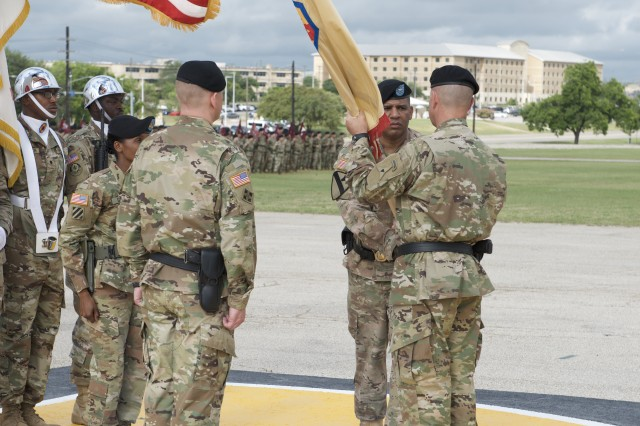 Outgoing 13th ESC Commanding General, Brig. Gen. Douglas McBride Jr., passes the 13th ESC colors to Maj. Gen. J. T. Thompson, III Corps and Fort Hood deputy commanding general during Thursday's Change of Command ceremony on Sadowski Field on Fort Hood, Texas May 24, 2018. (U.S. Army photo by Sgt. 1st Class Michael Cox)