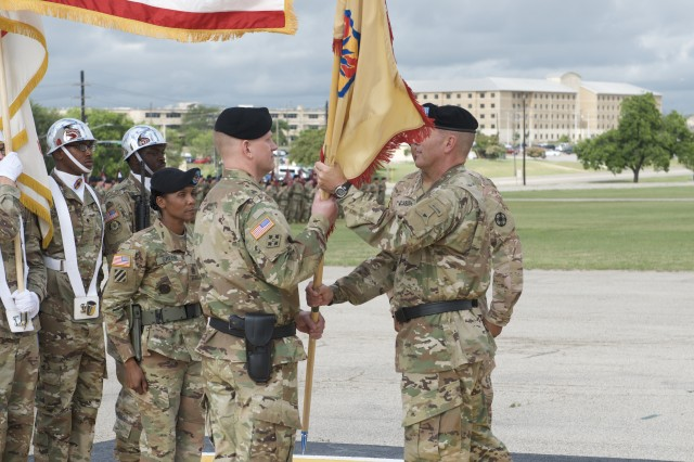 Incoming 13th ESC Commanding General, Brig. Gen. Darren L. Werner. Douglas, receives the 13th ESC colors from Maj. Gen. J. T. Thompson, III Corps and Fort Hood deputy commanding general during Thursday's ceremony on Sadowski Field on Fort Hood, Texas May 24, 2018. (U.S. Army photo by Sgt. 1st Class Michael Cox)