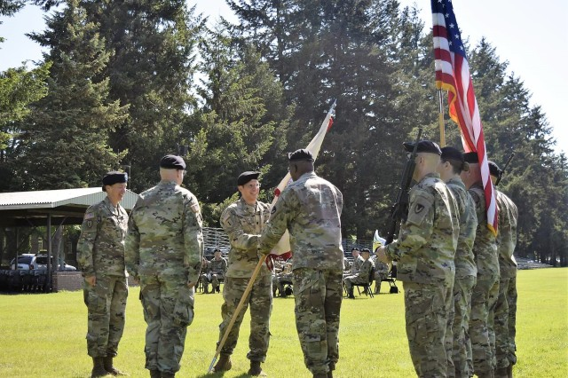 Lt. Col. Kevin Shilley passes the organizational colors of the 902nd Contracting Battalion to Sgt. Maj. Roderick Johnson during a change-of-command ceremony May 22 at Joint Base Lewis-McChord, Washington. Col. Lynda Armer, 418th Contracting Support Brigade commander, officiated the ceremony. Shilley took command to the battalion from Lt. Col. Toney Stephenson. Johnson is the battalion sergeant major.