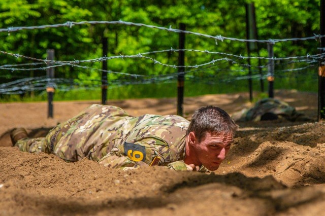 Cpl. Taylor Darwin, 3rd Brigade Combat Team, 101st Airborne Division (Air Assault), navigates the low crawl obstacle during the Best Air Assault Competition at The Sabalauski Air Assault School May 24 at Fort Campbell. This competition was part of the Day of the Eagles, and Air Assault qualified Soldiers of the 101st competed in various events such as a 12 mile road march, in hopes of being named the Best Air Assault team.