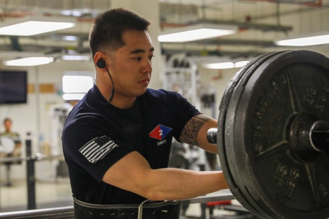 U.S. Army Sgt. Curtis Sua, an infantryman assigned to 2nd Infantry Brigade Combat Team, 4th Infantry Division, secures the weights on a barbell, May 17, 2018, at a physical fitness center on Kandahar Airfield, Afghanistan. Sua, a native of Las Vegas, Nevada, recently earned a spot as a member of the 1,000-pound club at the NATO physical fitness center. (U.S. Army photo by Staff Sgt. Neysa Canfield/TAAC-South Public Affairs)