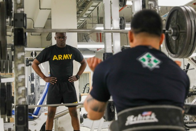 U.S. Army Spc. Tirmidhi Tucker, a signal support specialist with 2nd Infantry Brigade Combat Team, 4th Infantry Division, receives advice from U.S. Army Sgt. Curtis Sua, an infantryman assigned to 2IBCT, 4th Inf. Div., May 17, 2018, at a physical fitness center on Kandahar Airfield, Afghanistan. Sua, an infantryman assigned to 2IBCT, 4th Inf. Div., recently joined the 1,000-pound club at the NATO physical fitness center. (U.S. Army photo by Staff Sgt. Neysa Canfield/TAAC-South Public Affairs))