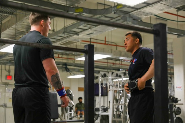 U.S. Army Spc. Justin Lacklore, left, an infantryman assigned to 2nd Infantry Brigade Combat Team, 4th Infantry Division, and U.S. Army Sgt. Curtis Sua, an infantryman assigned to 2IBCT, 4th Inf. Div., talk about their workout plan, May 17, 2018, at a physical fitness center on Kandahar Airfield, Afghanistan. Lacklore and Sua recently joined the 1,000-pound club at the NATO physical fitness center. (U.S. Army photo by Staff Sgt. Neysa Canfield/TAAC-South Public Affairs)