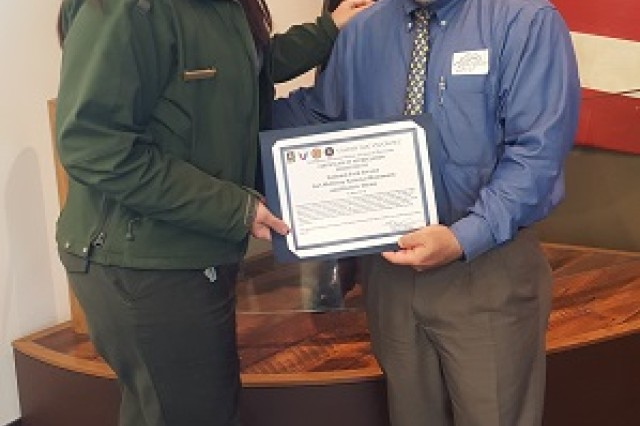 Mr. Michael Crapanzano presents a Memorandum and Certificate of Appreciation to Park Ranger Nicolette Talley, Fee Program Manager and Special Park Use Coordinator,  after the recent visit of staff of the U.S. Army Communications-Electronics Command Software Engineering Center Intelligence, Electronic Warfare, and Sensors Directorate to Fort McHenry for a leadership development session.