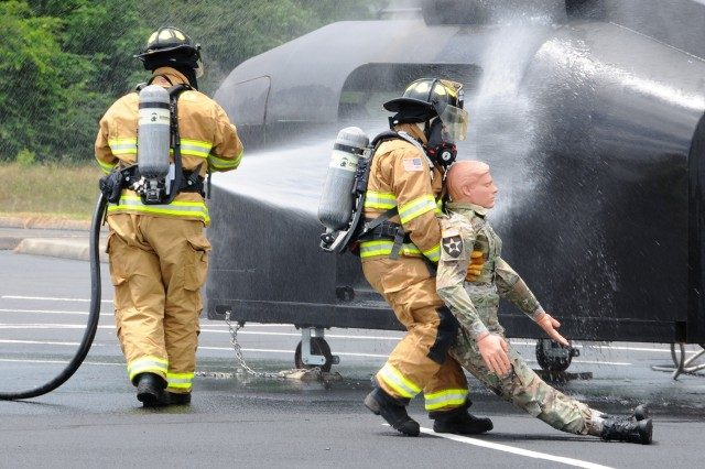 Rodney Taylor, Fort Rucker firefighter, retrieves a simulated crash survivor as fellow firefighter, Clayton Forston, continues to extinguish the flames during an exercise near Skelly Stagefield May 22.