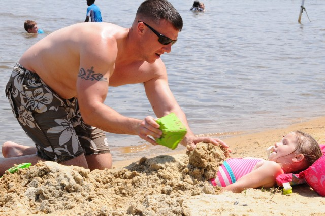 CW3 Andrew Northampton, 1st Battalion, 13th Aviation Regiment, buries his daughter, Amelia, in the sands of West Beach at Lake Tholocco during Day at the Lake May 19.