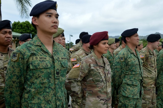 U.S. Soldiers assigned to the 3rd Brigade Combat Team, 25th Infantry Division; the 29th Infantry Brigade Combat Team, Hawaii Army National Guard; 426th Civil Affairs Battalion, California Army National Guard, and Singapore Soldiers assigned to the 6th Division, Singapore Army and 10th Singapore Infantry Brigade listen to closing remarks during the opening ceremony of Tiger Balm 18 at the 298th Regiment, Multi-Functional Training Unit (MFTU), Regional Training Institute (RTI), Waimanalo, Hawaii, on May 26, 2018. Tiger Balm is an annual bilateral military exercise designed to enhance the professional relationship, combat readiness, and interoperability between the US and Singapore, and fulfill and demonstrate regional security partnership and resolve. (U.S. Army photo by Staff Sgt. Armando R. Limon, 3rd Brigade Combat Team, 25th Infantry Division)