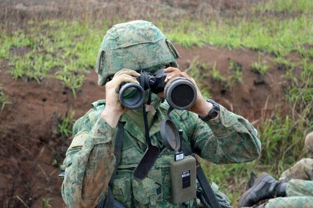 A Strike Observer Mission (STORM) team Soldier assigned to 24th Battalion Singapore Artillery scans the horizon at an observation post during a live fire exercise for Tiger Balm 18 at Schofield Barracks, Hawaii, on May 23, 2018. Tiger Balm is a bilateral exercise held yearly between the U.S. and Singapore armies. (U.S. Army photo by Staff Sgt. Armando R. Limon, 3rd Brigade Combat Team, 25th Infantry Division)