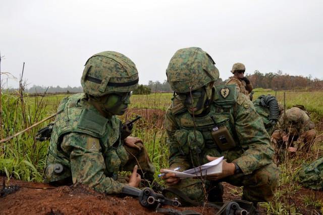 Cpl. 1st Class Jun Yi (right), a Strike Observer Mission (STORM) team Soldier assigned to 24th Battalion Singapore Artillery, discusses with a fellow Soldier about tactics during a live fire exercise for Tiger Balm 18 at Schofield Barracks, Hawaii, on May 23, 2018. Tiger Balm is a bilateral exercise held yearly between the U.S. and Singapore armies. (U.S. Army photo by Staff Sgt. Armando R. Limon, 3rd Brigade Combat Team, 25th Infantry Division)