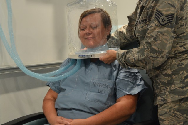Air Force Staff Sgt. Maribel Cortez, certified hyperbaric technician, places the oxygen hood on Christen Hesser to demonstrate how a patient would receive oxygen therapy in the multi-person chamber at the new Undersea & Hyperbaric Medicine Clinic at Brooke Army Medical Center June 13, 2017. If the patient is not comfortable with the hood, they can also wear a mask to receive their treatment.