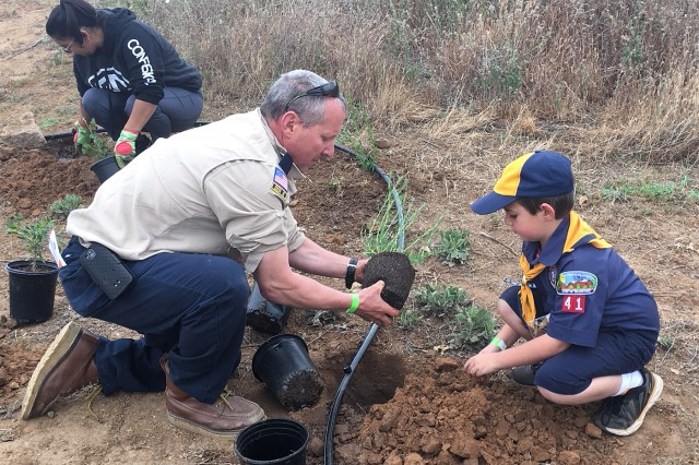 A Cub Scout and his leader prepare to plant native vegetation near the Santa Ana River during a May 12 community-restoration planting event in Norco, California. The event was hosted by the U.S. Army Corps of Engineers Los Angeles District, its contractor and the City of Norco as a joint effort to help restore the area to its natural habitat.