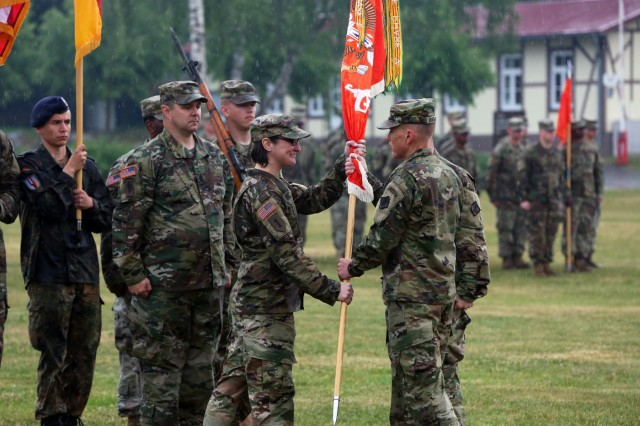 U.S. Army Col. Jeff Worthington, commander of the 2nd Theater Signal Brigade, passes the 44th Expeditionary Signal Battalion colors to incoming commander Lt. Col. Heather McAteer during a change of command ceremony May 24, 2018 on the Tower Barracks Parade Field in Grafenwoehr, Germany. (U.S. Army photo by William B. King)