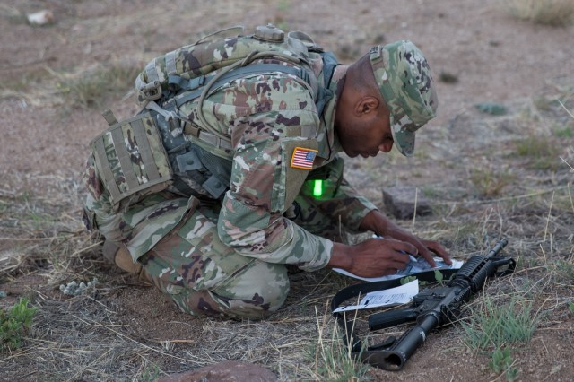 Pfc. Askia Humphrey, from the 111th Military Intelligence Brigade, begins to plot his points as the sun sets for the Night Land Navigation Course during the U.S. Army Intelligence Center of Excellence and Fort Huachuca's 2018 Best Warrior Competition.