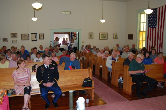 The audience gathers before a Memorial Day observance sponsored by the Scott County (Iowa) Historical Society held at historic Summit Church in rural Davenport, Iowa, May 28.  Sitting in the front pew is Maj. Timothy Oysti, chief of operations in the Command Operations and Information Center at the U.S. Army Sustainment Command, who served as guest speaker. Photo by Paul Levesque, ASC Public Affairs)
