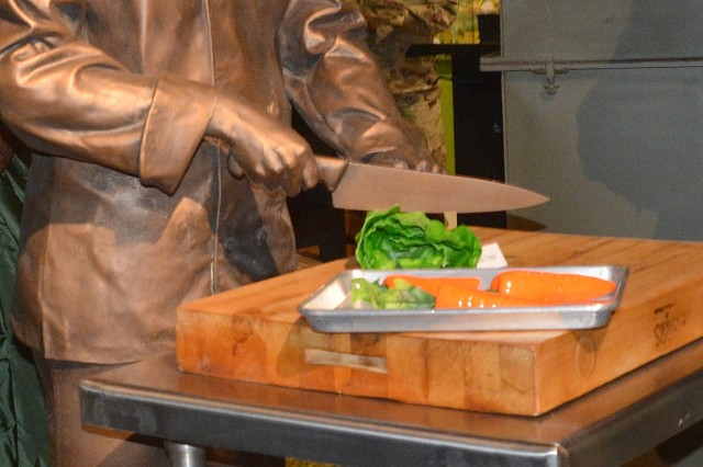 A statue paying tribute to culinary specialists was unveiled during a ceremony May 1 at the Quartermaster Museum. The lifelike bronze casting (also pictured right) depicts a culinarian chopping vegetables. An actual culinary specialist, Sgt. 1st Class Stephanie Owens, modeled for the likeness in February 2016. (Photo by Amy Perry, Fort Lee Public Affairs)