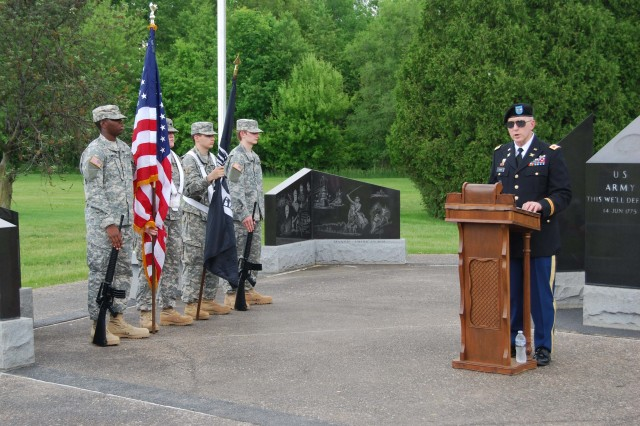 Col. Bradley Cook, inspector general for the U.S. Army Sustainment Command, speaks at a Memorial Day observance held at the All Veterans Memorial at Davenport Memorial Gardens, Davenport, Iowa, May 27.  A color guard from Military Explorers Post 944 stands to the left. (Photo by Paul Levesque, ASC Public Affairs)
