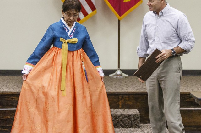 Dr. Helen Kim showcases the traditional Korean dress she wore as she gave a presentation to Anniston Army Depot's lunch and learn audience. ANAD Chief of Staff Phil Trued is also pictured as he prepares to present Kim with a certificate of appreciation.