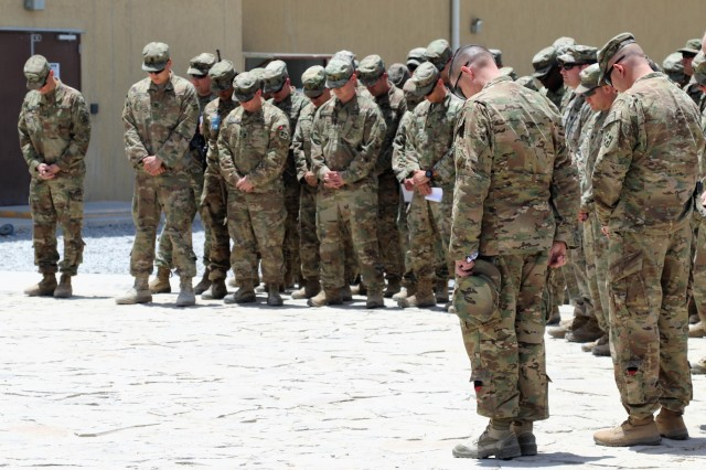 Soldiers and leaders bow their heads during an opening prayer of a Memorial Day observance at the Train, Advise, and Assist Command-South Headquarters in Kandahar, Afghanistan, May 28, 2018.  The prayer was given by Chaplain (Maj.) Patrick Devine, chaplain for TAAC-South. TAAC-South, commanded by Brig. Gen. John Lathrop, is composed of Soldiers from the 40th Infantry Division, California National Guard and the 2nd Infantry Brigade Combat Team, 4th Infantry Division. (U.S Army photo by Maj. Richard Barker/TAAC-South Public Affairs)
