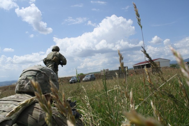 A Soldier bounds forward toward cover while another suppresses the enemy during Advanced Rifle Marksmanship and Individual Movement Techniques training May 24 at Camp Marechal De Lattre De Tassigny, Kosovo.