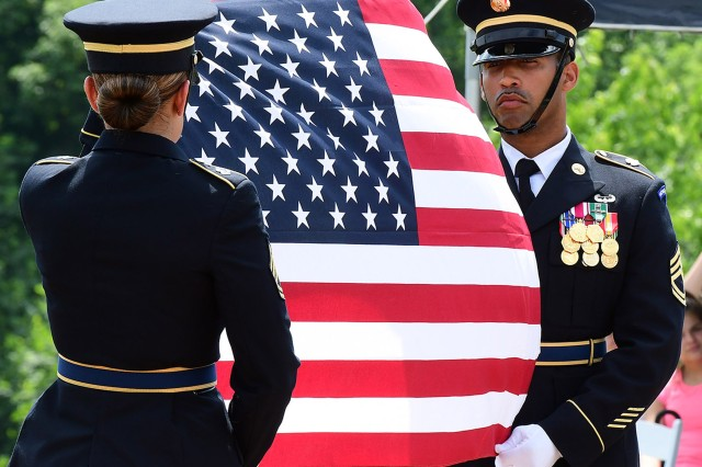 Sergeants 1st Class Golan Perry (right) and Joanna Carter prepare to fold the flag during a Memorial Day ceremony at the Kentucky Veterans Cemetery Monday.