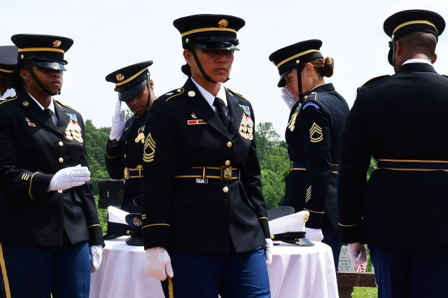 Members of the U.S. Army Human Resources Command honor guard salute the prisoners of war / missing in action table, a representation of those who have no returned from the battlefield.