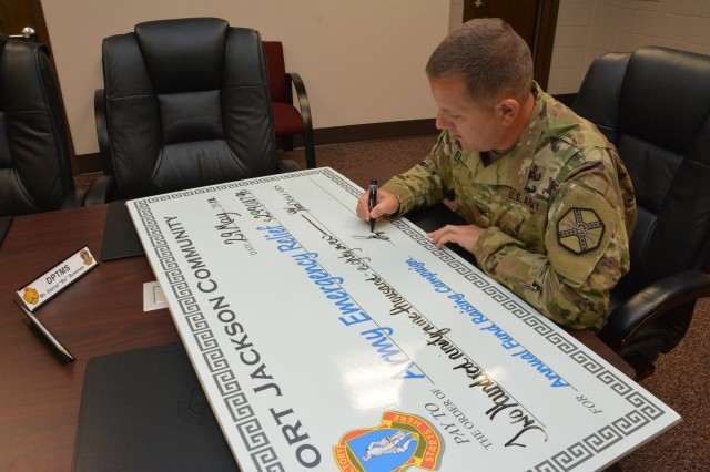 Col. Stephen Elder, Fort Jackson Garrison Commander, signs an Army Emergency Relief check for $299,087.96 May 29 at his office .The funds are donated by and used to assist Soldiers and Families with scholarships, grants interest-free loans in times of need such as emergency travel, minor home repairs, and health care expenses. Since its founding in 1942, AER has provided more than $1.8 billion to over 3.7 million Soldiers and Families in interest-free loans and grants.