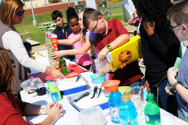 Children pour out portions of cereal during a youth health fair April 5 to determine how much sugar they consume during a typical morning breakfast.